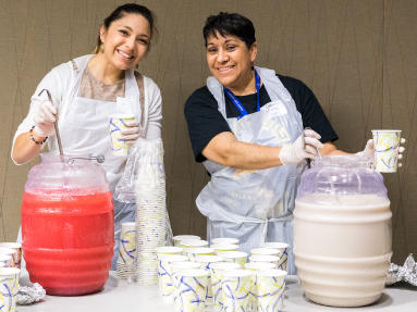 Two women working at an event are ready to serve soft drinks.