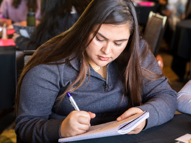 A student attending a workshop is writing in her notebook.