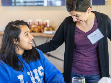 Program Director Lilly Pinedo is speaking with a student sitting at a table.