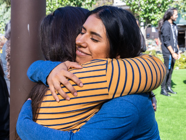 Two students share a friendly embrace at a group event.