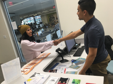 A student from behind the counter greets another student by shaking her hand.