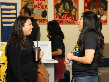 Two women have a conversation while other students wait in line behind them.