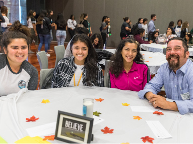 Group of four Chicanx/Latinx people sitting at a table.