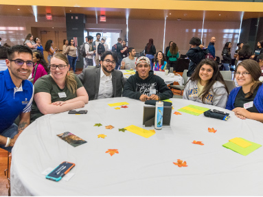 Diverse students around a table, while other students sit and stand behind them