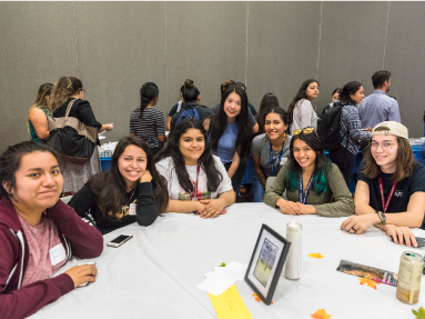 Seven students gathered around a table at an SJSU event.